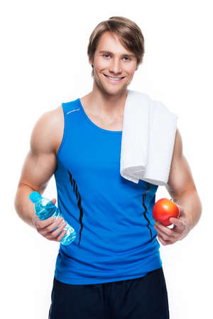 Portrait of handsome happy sportsman in blue shirt holds water and apple over white background. photo