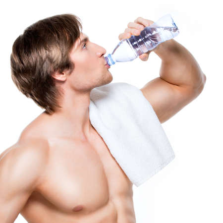 Handsome muscular shirtless sportsman drinks water - isolated on white background. photo