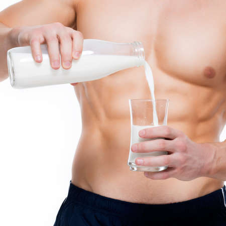 Young man with perfect body pouring milk into a glass - isolated on white background. photo