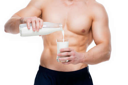 body milk: Young man with perfect body pouring milk into a glass - isolated on white background.