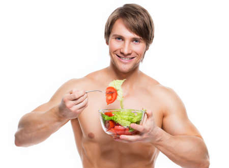 Young happy muscular man eating a salad over white background. photo