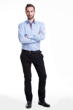 white pants: Portrait of serious man in blue shirt and black pants with crossed arms - isolated on white.