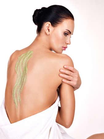 tratamientos corporales: Hermosa mujer adulta se preocupa por la piel del cuerpo con ungüento cosmético en la parte posterior - aislada en blanco. Concepto de tratamiento de belleza.