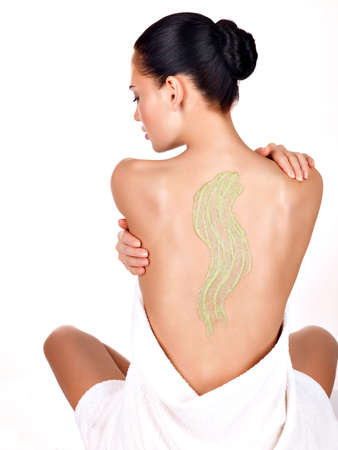naked woman  white background: woman cares about skin of body using cosmetic scrub on the back - isolated on white. Beauty treatment concept.