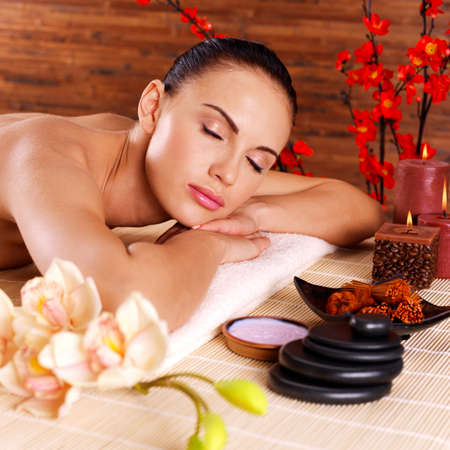 Adult beautiful woman relaxing in spa salon. Beauty treatment therapy photo