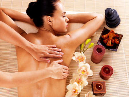 candles spa: Adult woman in spa salon having body relaxing massage.