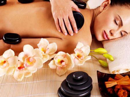 spas: Erwachsene Frau mit Hot-Stone-Massage im Wellness-Salon. Schönheitspflege-Konzept.