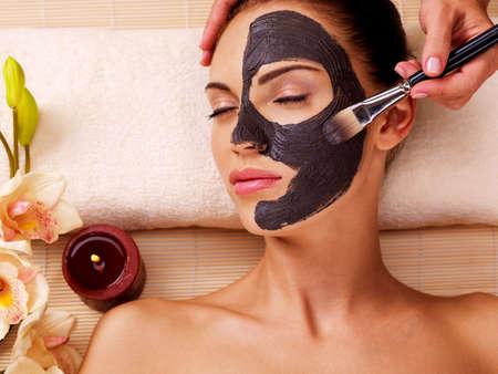 Frottis cosmétologue masque cosmétique sur le visage de la femme dans le salon de la sève