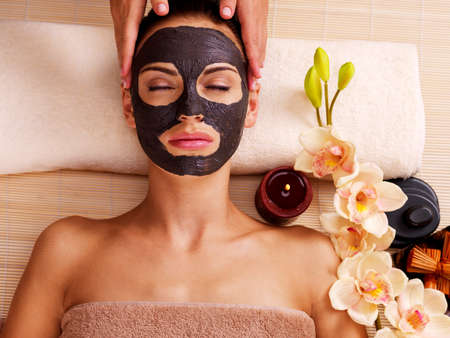 Schoonheidsspecialist die massage op het gezicht van de vrouw in sap salon. Vrouw met scrub cosmetische masker op het gezicht.