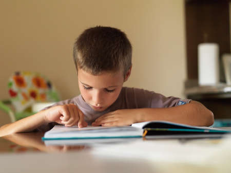 one child: Portrait of focused boy reading a book while sitting at table at home.