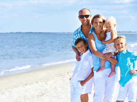 Happy smiling family with children standing on the sunny beach.