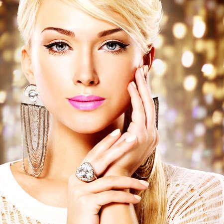 rubia ojos azules: Retrato de una mujer hermosa con los labios de color rosa brillante y maquillaje de moda. Posando en el estudio sobre el fondo de arte Modelo