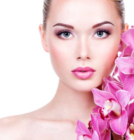 Detailní záběr na tvář mladé krásné ženy s make-up fialové očí a rtů. Pretty dospělých dívka s květinami v blízkosti obličeje. - Izolovaných na bílém pozadí
