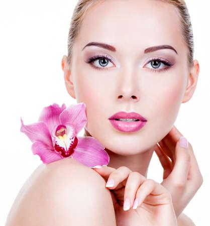 orchidee: Viso Primo piano di una giovane donna bella con un trucco degli occhi viola e le labbra. Bella ragazza adulta con fiore vicino al viso. - Isolato su sfondo bianco