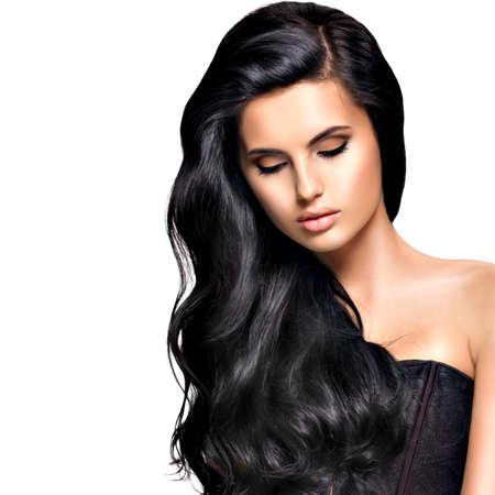Hermosa mujer morena con el pelo largo y rizado negro posando en el estudio