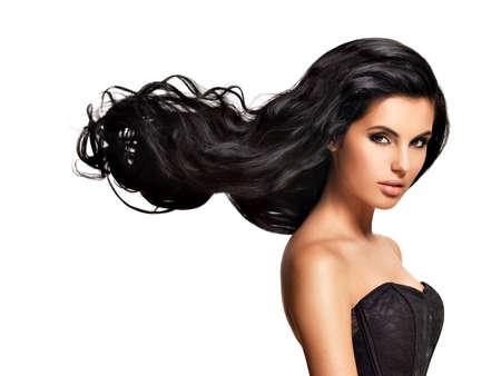černé vlasy: Krásná mladá brunetka žena s dlouhými černými kudrnatými vlasy představují ve studiu LANG_EVOIMAGES