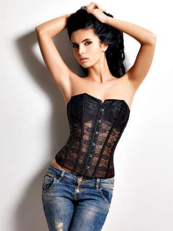 corset: Full portrait of the beautiful young sexy woman with long black  hair posing at studio dressed in the jeans and corset
