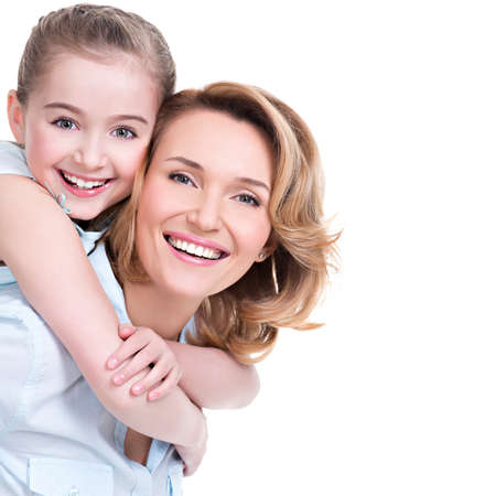 toothy: CLoseup portrait of happy  white mother and young daughter - isolated. Happy family people concept.