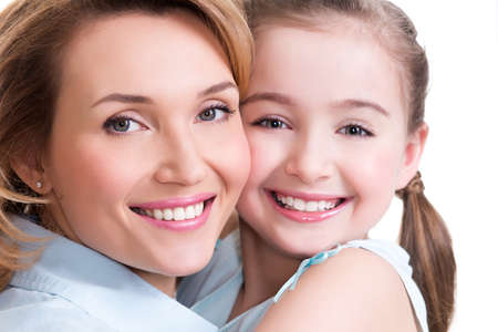 two girls hugging: CLoseup portrait of happy  white mother and young daughter - isolated. Happy family people concept.