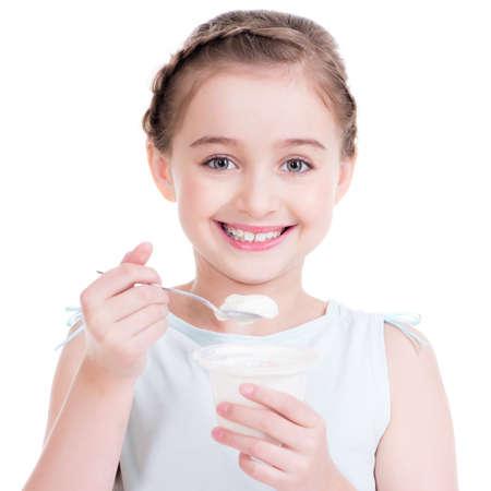 Portrait d'une petite fille de manger du yogourt - isolé sur blanc.