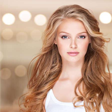 Portrait de la belle jeune femme aux longs cheveux bouclés. Gros plan d'un visage joli modèle caucasien regardant la caméra Banque d'images - 33624701