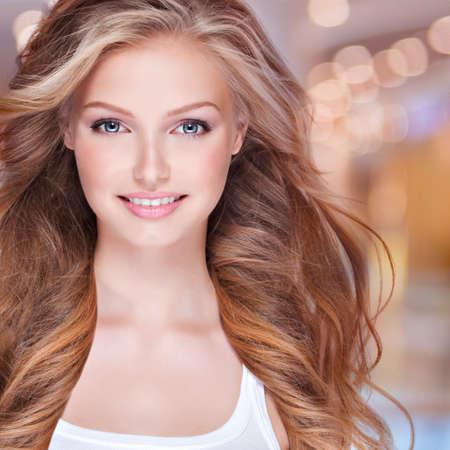 blonde yeux bleus: Portrait de la belle jeune femme heureuse avec de longs cheveux bouclés. Visage d'un joli modèle souriant regardant la caméra