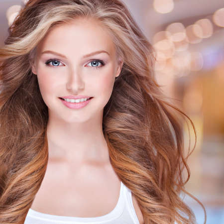 Portrait of beautiful happy young woman with long curly hair. Face of a smiling pretty model looking at camera Stock Photo