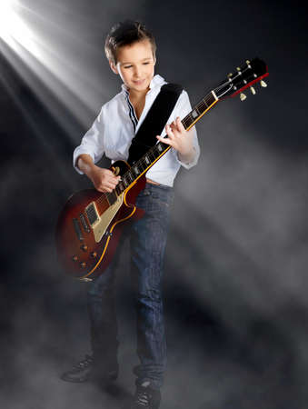 music stage: A young white boy sings and plays on the electric guitar on the stage with bright lights