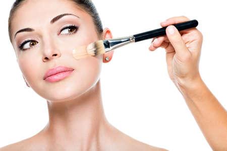 liquido: Artista de maquillaje que aplica la fundación tonal líquido en la cara de la mujer LANG_EVOIMAGES