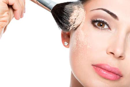 Portrait Gros plan d'une femme appliquant Fondation tonale cosmétique sèche sur le visage à l'aide pinceau de maquillage.