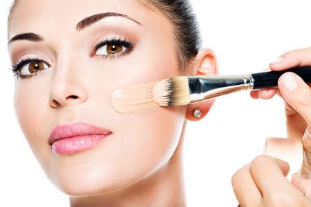 Maquilleur appliquer fondation tonale liquide sur le visage de la femme