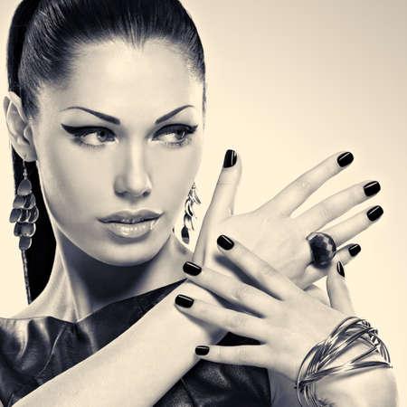 Vrouw met zwarte nagels en met stijlvolle sieraden. Zwart of wit concept afbeelding