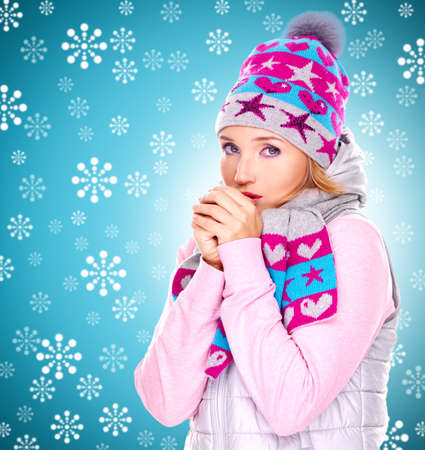 beautiful young woman in winter clothes warming her hands with snow falls photo