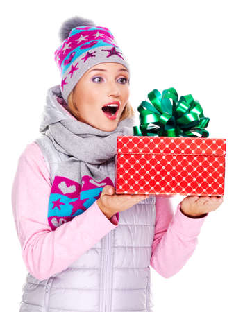 outerwear: Photo of happy surprised woman with a christmas gift in a winter outerwear - isolated on white