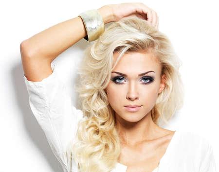 長い巻き毛の髪とスタイルの化粧品で美しい金髪の女性。白い背景とポーズの女の子 写真素材