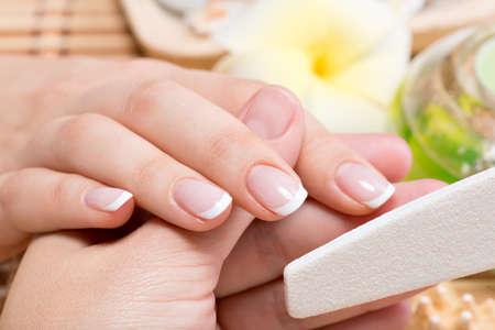 mimos: Mujer en un salón de uñas recibiendo manicura por una esteticista. Concepto de tratamiento de belleza.