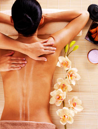 laying on back: Adult woman in spa salon having body relaxing massage.