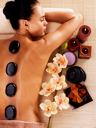 laying on back: Adult woman relaxing in spa salon with hot stones on body. Beauty treatment therapy