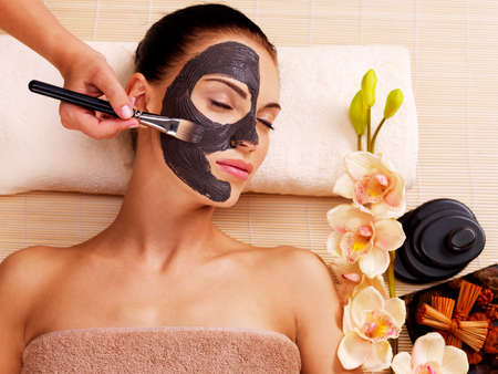 cosmetologist: Cosmetologist smears cosmetic mask on the face of the woman in the sap salon