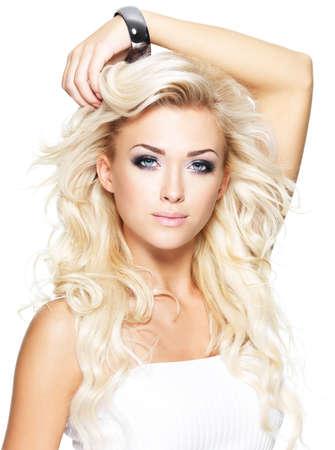 Portret van mooie blonde vrouw met lang krullend haar - op wit wordt geïsoleerd