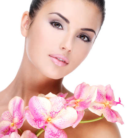 Beautiful face of young pretty woman with healthy skin and pink flowers on body - isolated on white photo
