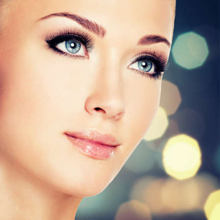 Porträt einer Frau mit schönen blauen Augen und langen schwarzen Wimpern - studio shot LANG_EVOIMAGES