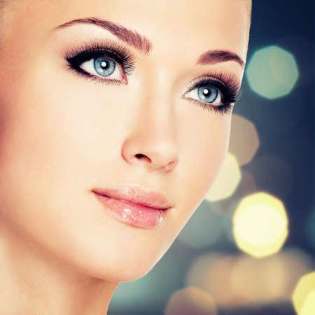 Retrato de una mujer con hermosos ojos azules y pestañas largas y negras - tiro del estudio
