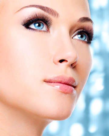 false eyelash: Portrait of  a  woman with beautiful blue eyes and long black eyelashes  - studio shot