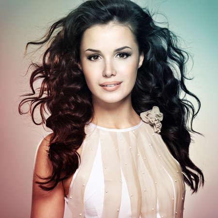 dishevel: Bella giovane donna con lunghi capelli castani. Modello grazioso pone in studio. Concetto di immagine � nella colorazione stile colorize LANG_EVOIMAGES