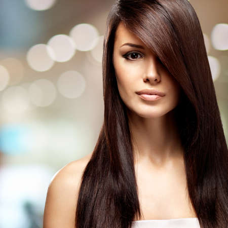 Beautiful woman with long straight brown hair. Fashion model posing at studio over art creative background