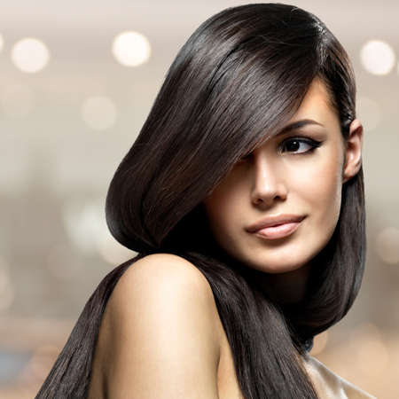 Beautiful woman with long straight hair. Fashion model posing Фото со стока