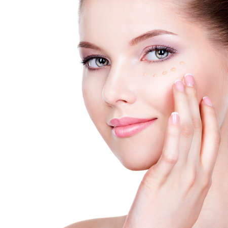 白い背景の上の皮膚にファンデーションを持つ若い女性の美しい顔。美容治療の概念。