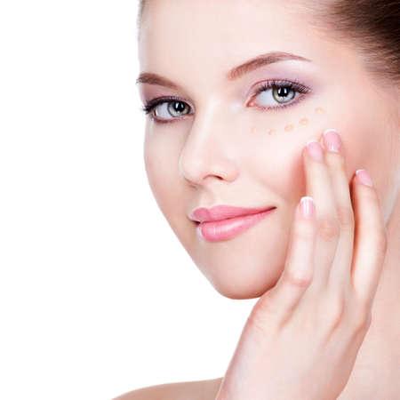 mujer maquillandose: Hermoso rostro de mujer joven con la fundaci�n de cosm�tico en la piel sobre el fondo blanco. Concepto de tratamiento de belleza.
