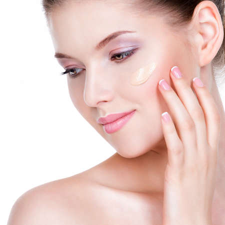 background beauty: Beautiful face of young woman with cosmetic foundation on a skin over white background. Beauty treatment concept.
